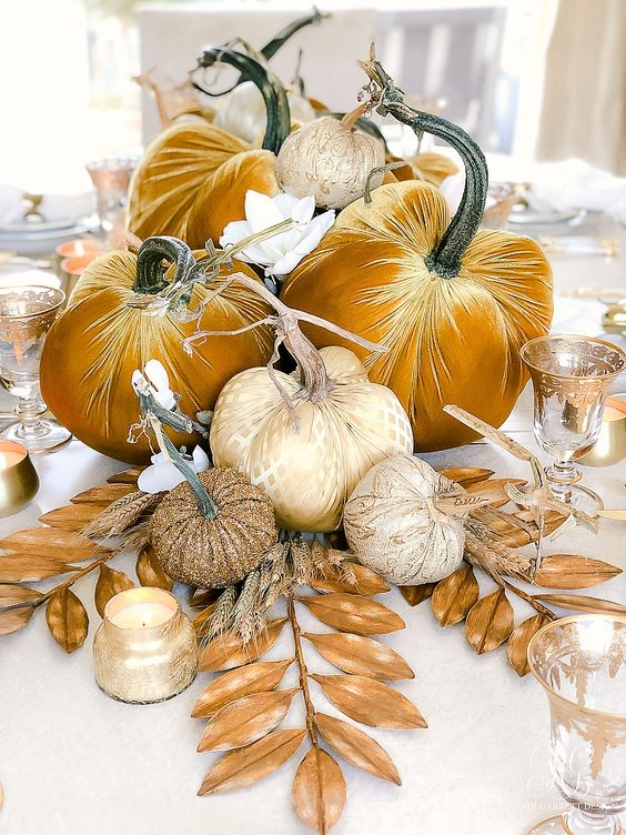 a bright fall centerpiece of mustard velvet pumpkins and glam printed ones, gilded leaves and candles is lovely and refined