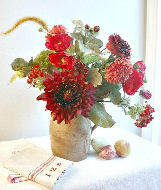 a bright fall centerpiece of red and burgundy blooms, greenery in a vintage jug is a bold decoration