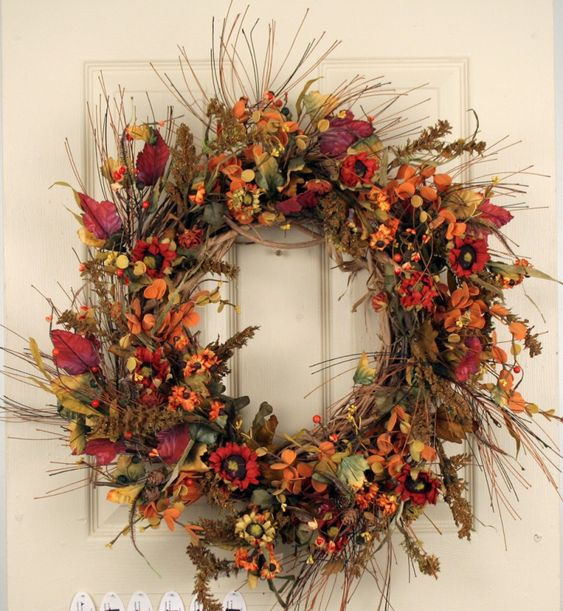 a bright fall twig wreath with lots of bold faux leaves, blooms, berries and fruits is a statement decoration