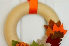 a bright fall wreath covered with neutral yarn, colorful fabric leaves and flowers is easy to make yourself