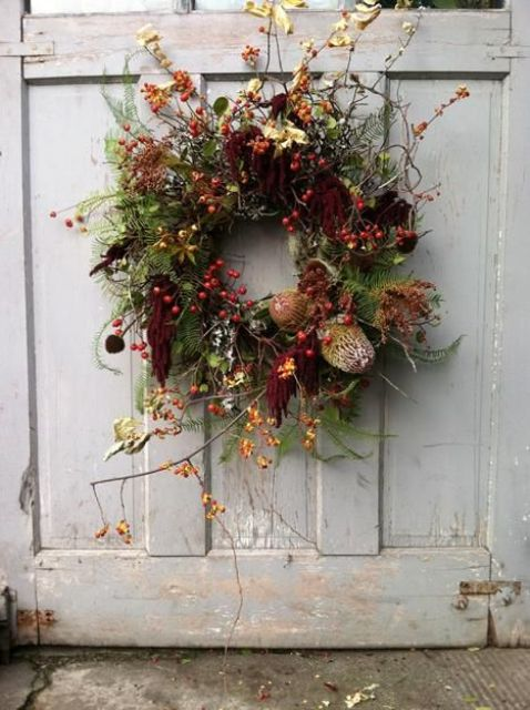 a bright fall wreath with twigs, berries, dark blooms, fabric ribbons and dried flowers is very refined