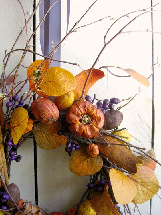 a bright fall wreath with twigs, berries, faux veggies and fruits, bright leaves is a harvest-inspired piece