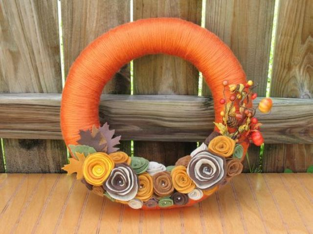 a bright orange yarn wreath decorated with fabric flowers, leaves, berries and dried blooms