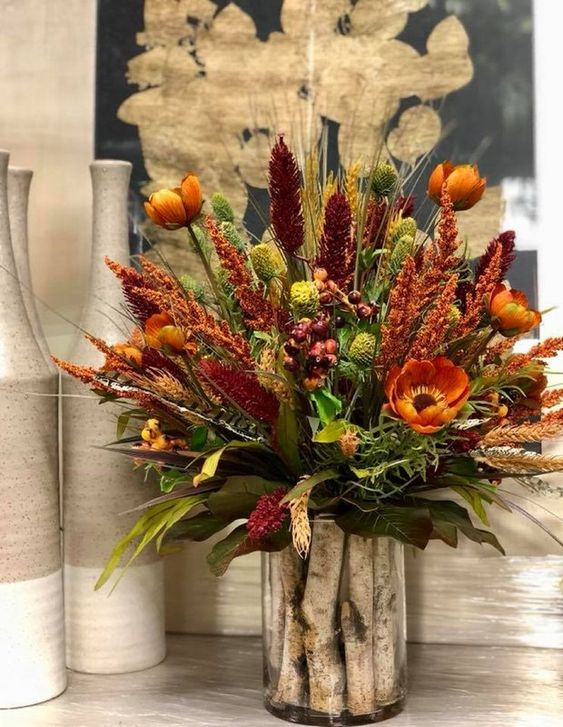 a bright rustic arrangement of rust, burgundy faux blooms, dried herbs and greenery and wooden sticks in the vase