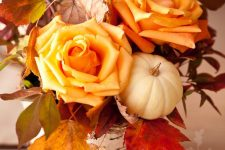 a bright rustic fall centerpiece of orange roses, fall leaves, a white pumpkin and a vase wrapped white bark