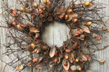 a brigth natural fall wreath with twigs, acorns, berries, pinecones is lovely way to add a woodland feel to the space