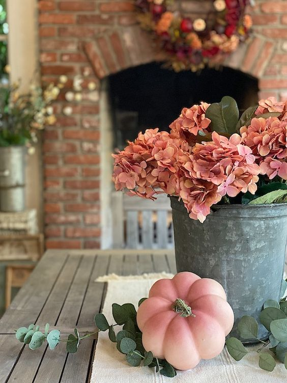 a bucket with pink hydrangeas and leaves plus a matching pink pumpkin next to it is a stylish rustic idea