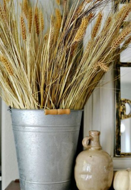 a bucket with wheat is a cool rustic decoration for the fall, it's veyr easy to compose