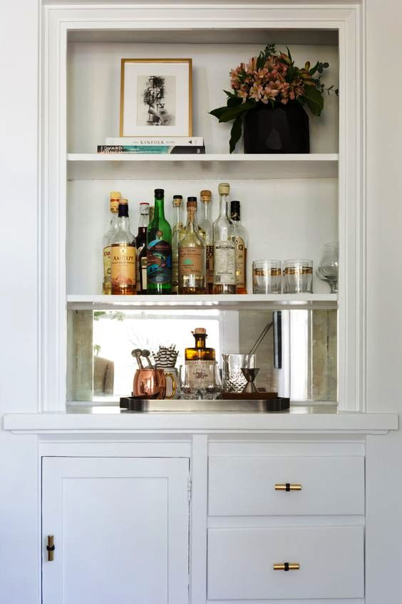 a built-in bar with some open shelves and closed storage compartments is a cool space-saving idea