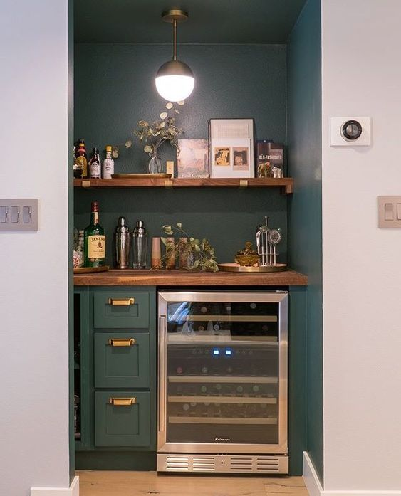 a built-in home bar with an open shelf, drawers and a fridge plus some greenery is a chic idea
