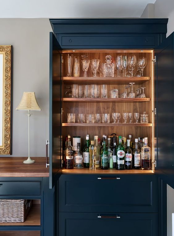 a built-in home bar with open shelves with lights and drawers for storage is a very cool idea to rock