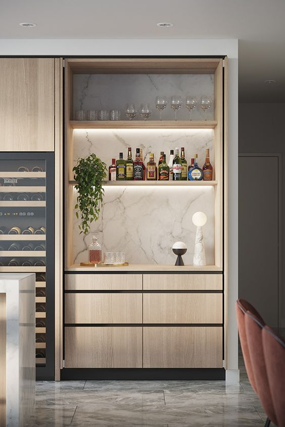 a built-in minimalist mini bar in the kitchen, with a marble backsplash, built-in shelves with lights and sleek drawers