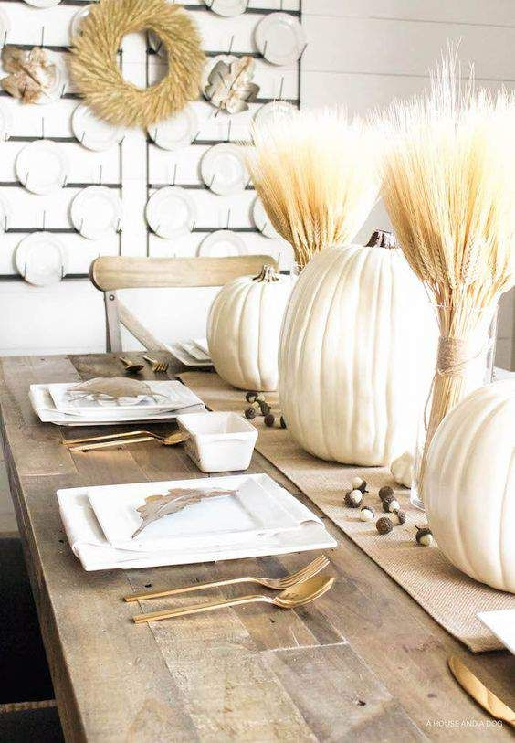 a burlap table runner with acorns, white pumpkins, wheat bundles in vases for a vintage farmhouse tablescape