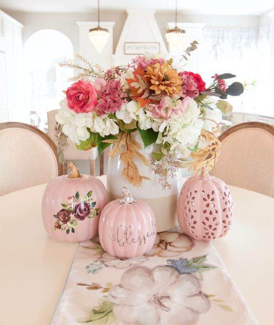 a chic and bright fall flower arrangement of white, pink, rust blooms and greenery and pink faux pumpkins
