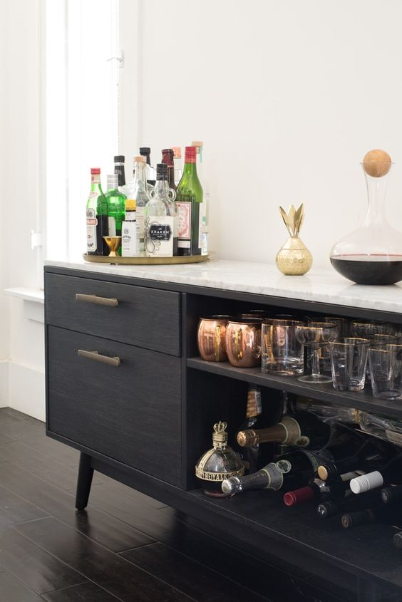 a chic black home bar with open and closed storage compartments, gold touches and a gold tray is elegant