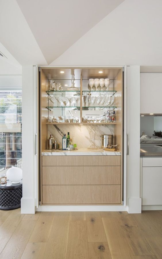 a chic built-in home bar with a marble backsplash, a mirror, glass shelves and sleek drawers for a modern space