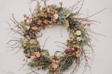 a chic twig fall wreath with moss, berries, twigs, dried leaves and blooms plus pinecones for a fall feel
