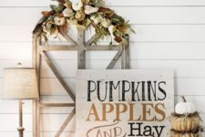 a chic whitewashed wooden sign with black and rust-colored letters, pumpkins and candles around