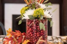a chic woodland fall centerpiece of a wood slice, antlers, fall leaves, a glass with cranberries, blooms and leaves