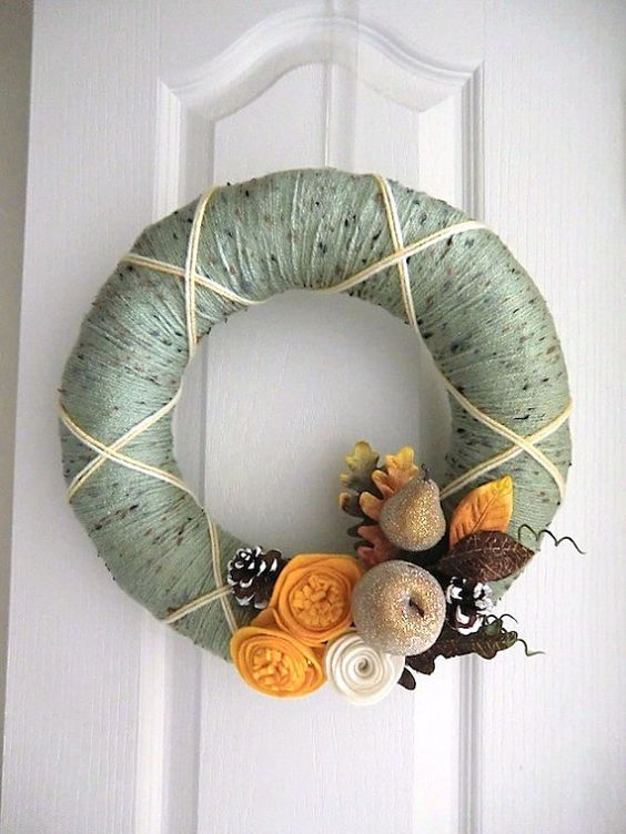 a chic yarn wreath with green yarn, fabric flowers and leaves and glitter fruit and snowy pinecones looks unusual