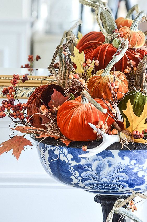 a chinoiserie bowl with fall leaves, berries, antlers, bright velvet pumpkins is a fantastic fall centerpiece