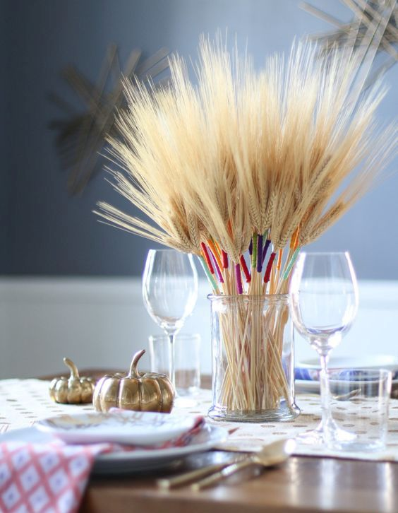 a clear jar with wheat wrapped with colorful twine is a bold and fun fall centerpiece to try