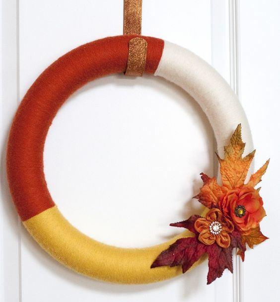a color block fall wreath covered with rust, yellow and white yarn, with faux blooms and leaves