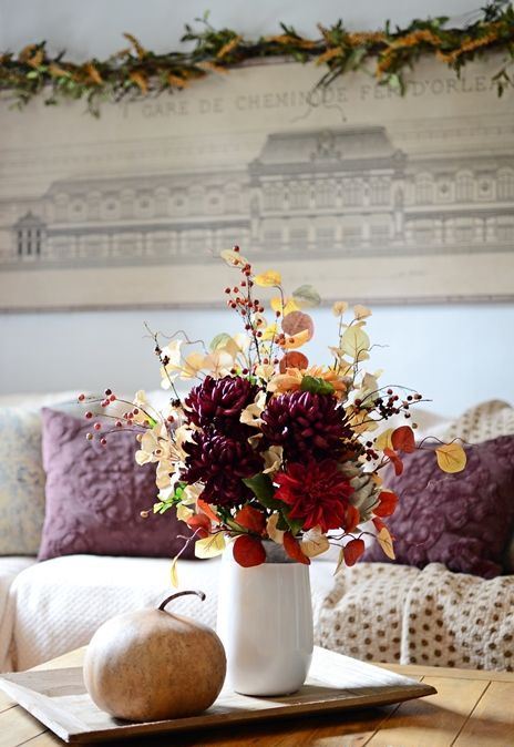 a colorful fall arrangement of leaves, branches with berries, faux bright blooms and a large veggie next to it