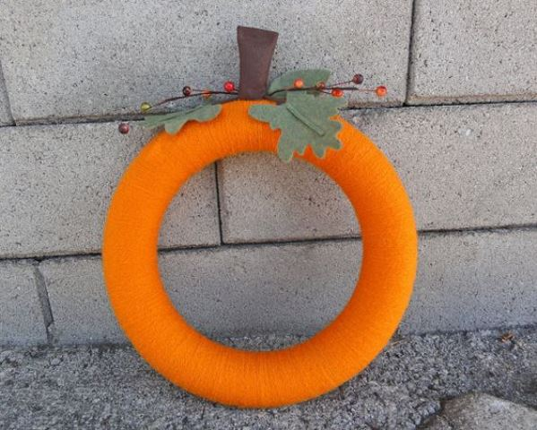 a colorful fall wreath covered with orange yarn, with fabric leaves and berries imitates a pumpkin