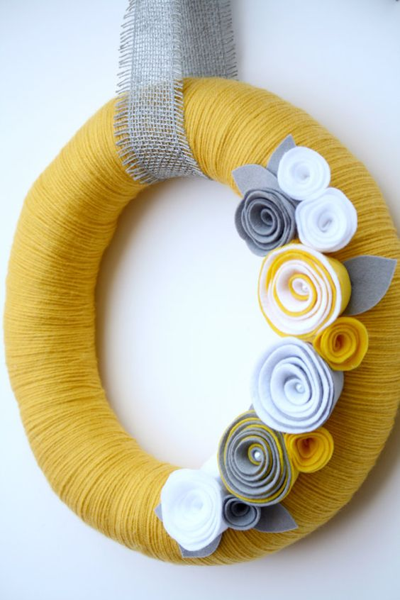 a colorful fall wreath covered with yellow yarn, fabric flowers and a burlap ribbon for a bold look