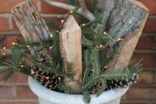 a concrete planter with pinecones, fir branches, firewood and lights is a cool outdoor decoration