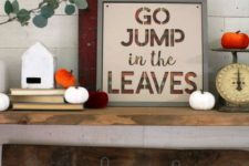 a contemporary fall sign with letters in bright orange and lots of fabric pumpkins around