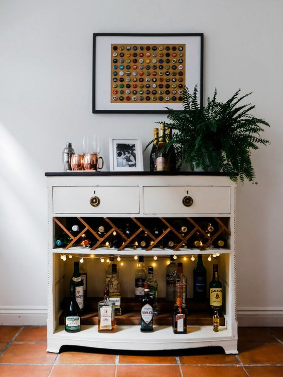 a cool bar unit with open space with lights, drawers and a potted plant plus a catchy artwork of lids