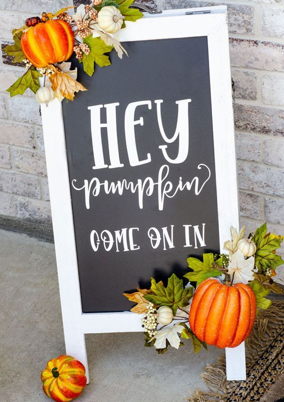 a cool black and white fall sign decorated with faux leaves ad pumpkins is a cool fall decoration for outdoors