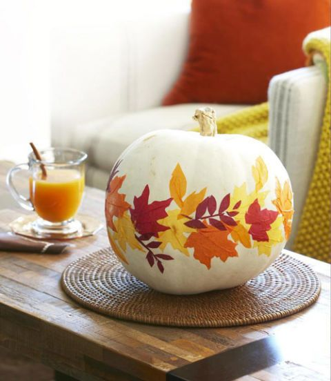 a cool pumpkin centerpiece with bright fall leaves attached is an amazing fall decoration