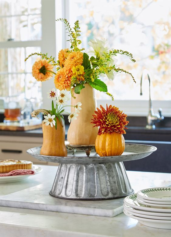 a cool rustic decoration of a metal stand with gourds and pumpkins plus greenery and faux bright blooms