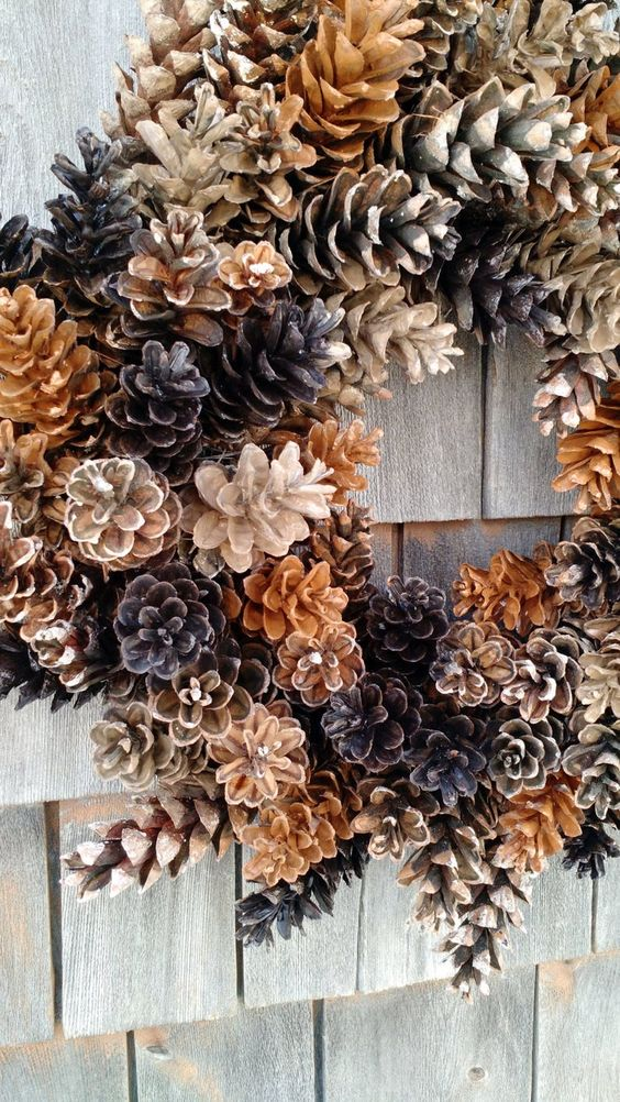 a cool wreath of pinecones of various shades is a very cool fall to winter decoration for your front door