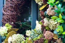 a creative fall wreath of white hydrangeas, vine, pinecones, greenery, gourds, mushrooms and greenery looks very eye-catchy