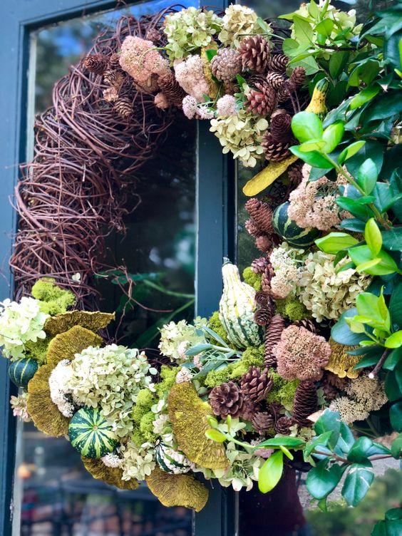 a creative fall wreath of white hydrangeas, vine, pinecones, greenery, gourds, mushrooms and greenery looks very eye catchy
