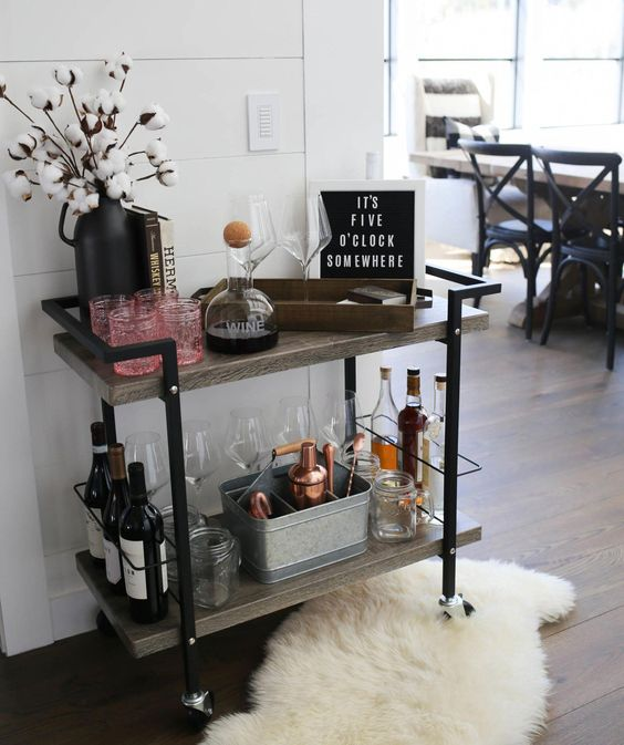 a creative plywood and metal bar cart with some cotton branches, artworks, open storage compartments