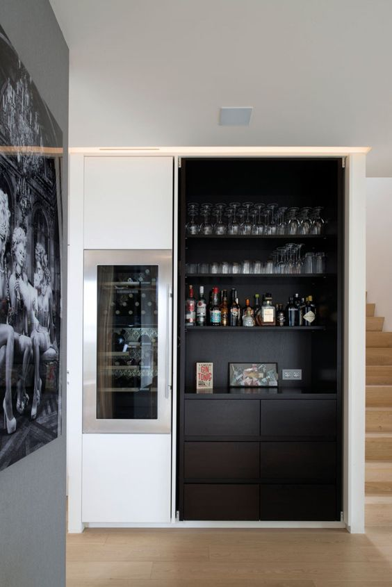 a dark built-in home bar with open shelves, artworks and sleek drawers is very stylish and chic