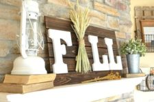 a dark stained Fall sign with white letters and a pack of wheat right in the center for a rustic touch