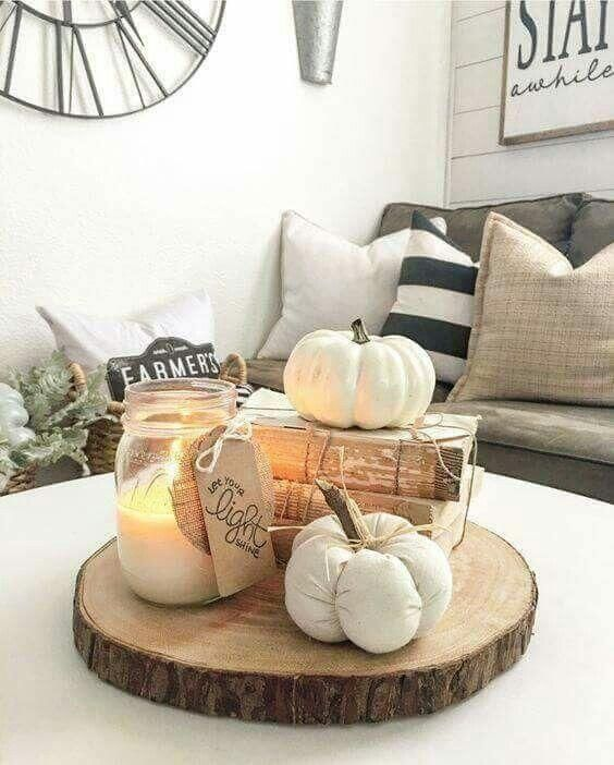a fall arrangement of a wood slice, vintage books, faux pumpkins and a candle in a jar is very easy and cool