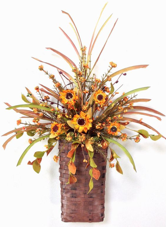 a fall arrangement of foliage, berries and bright orange faux blooms in a basket is a stylish decoration
