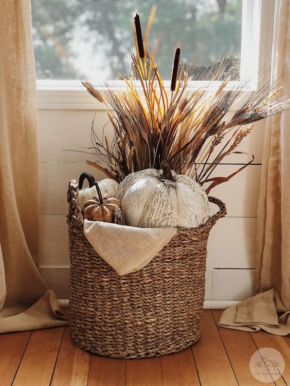 a fall basket styled with faux pumpkins, wheat, cane and burlap is a cool rustic arrangement