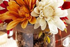 a fall centerpiece of a glass vase, pinecones, twine and bright and white flowers is very easy to compose