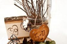 a fall centerpiece of a wood slice, moss, greenery, a wooden heart, a wooden piece and some branches and twigs in a glass vase