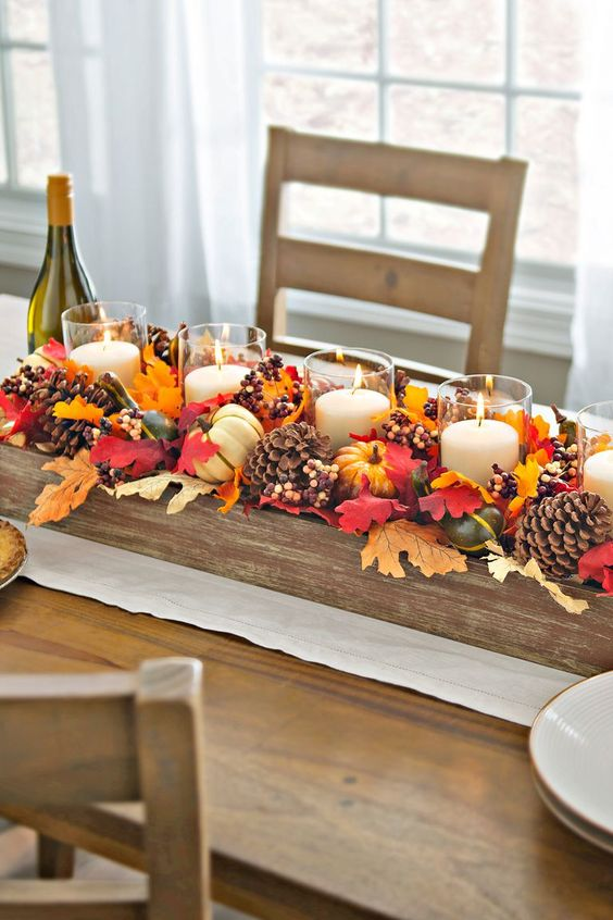 a fall centerpiece of a wooden box with pinecones, berries, fall leaves and candles in glass candle holders
