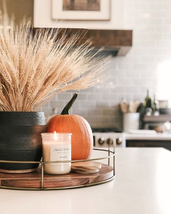 a fall centerpiece of a wooden tray, a candle in a jar, a pumpkin and wheat in a planter is a cool idea