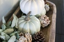 a fall decoration of a wooden bowl with pinecones, white faux pumpkins, green balls and pale leaves